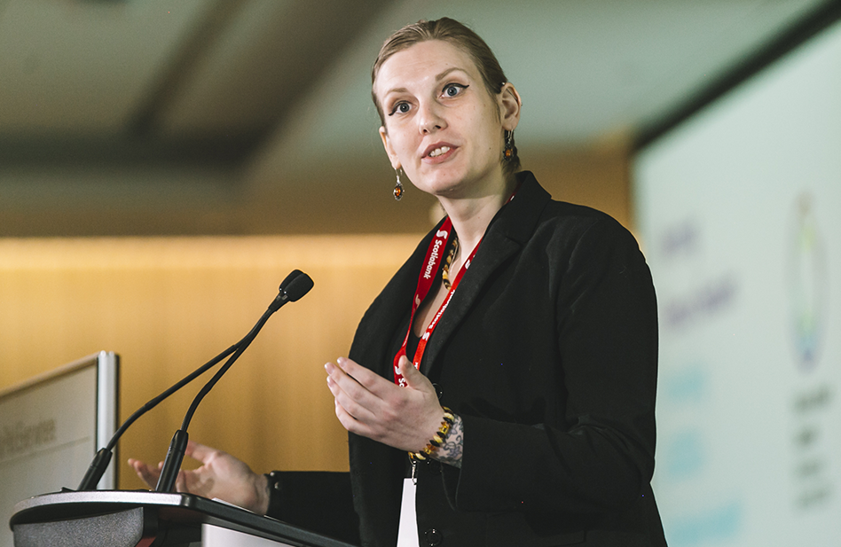 A woman named Jade speaking at a podium to an audience